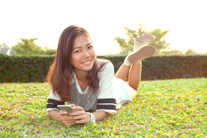 Retrato de la mujer joven hermosa que miente en campo de hierba verde y foto de archivo libre de regalías