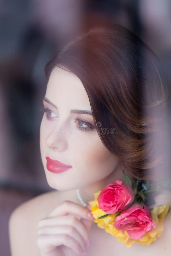 Retrato de la mujer joven hermosa que se coloca cerca de la ventana y del l foto de archivo libre de regalías