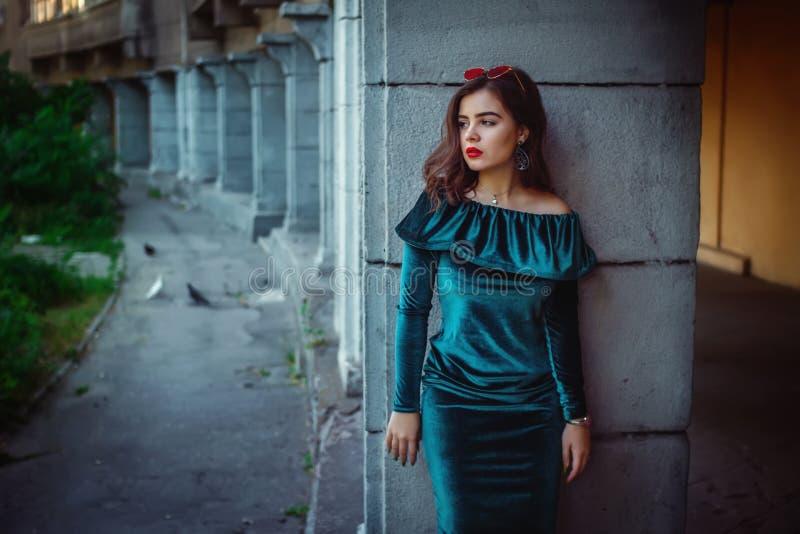 Retrato de la mujer joven hermosa que se coloca cerca del edificio viejo fotos de archivo