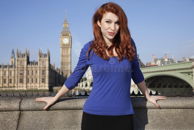 Retrato de la mujer joven hermosa que se opone a la torre de reloj de Big Ben, Londres, Reino Unido fotografía de archivo