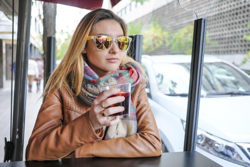 Retrato de la mujer joven hermosa que se sienta en café de la calle fotografía de archivo libre de regalías