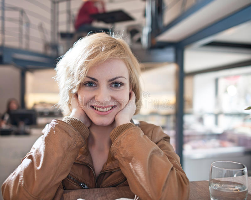 Retrato de la mujer joven hermosa que sonríe en café imagen de archivo
