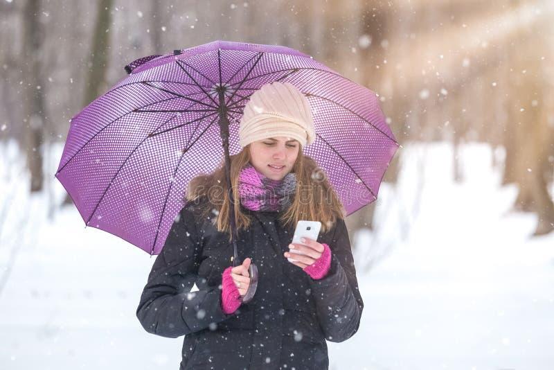 Retrato de la mujer joven hermosa que sostiene el teléfono móvil en día nevoso foto de archivo