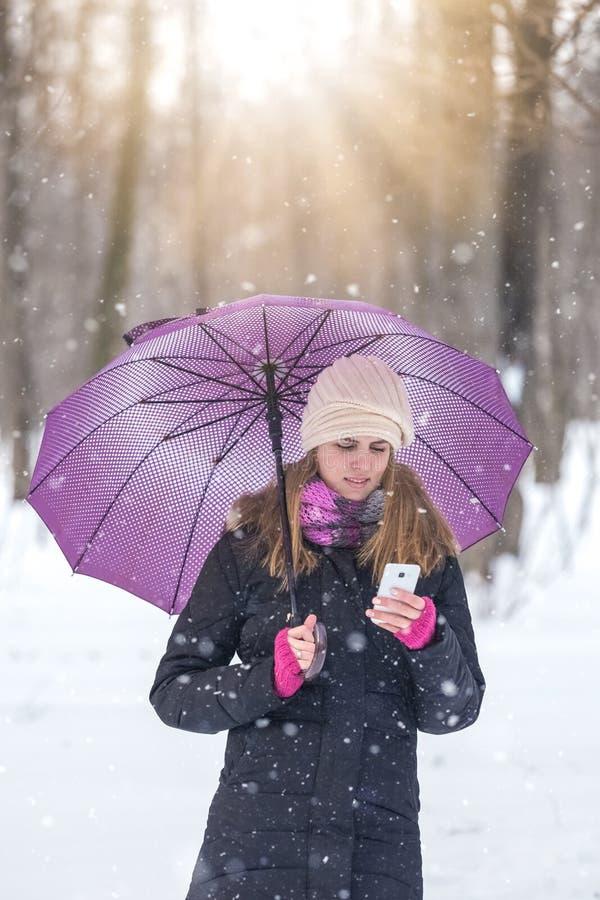 Retrato de la mujer joven hermosa que sostiene el teléfono móvil en día nevoso fotografía de archivo