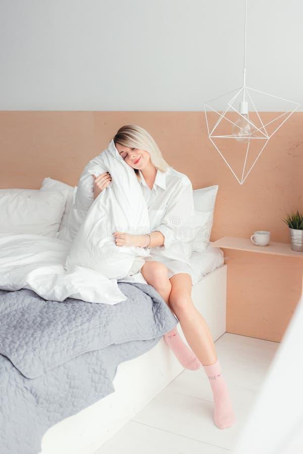 Retrato de la mujer joven hermosa que sostiene una almohada imagen de archivo