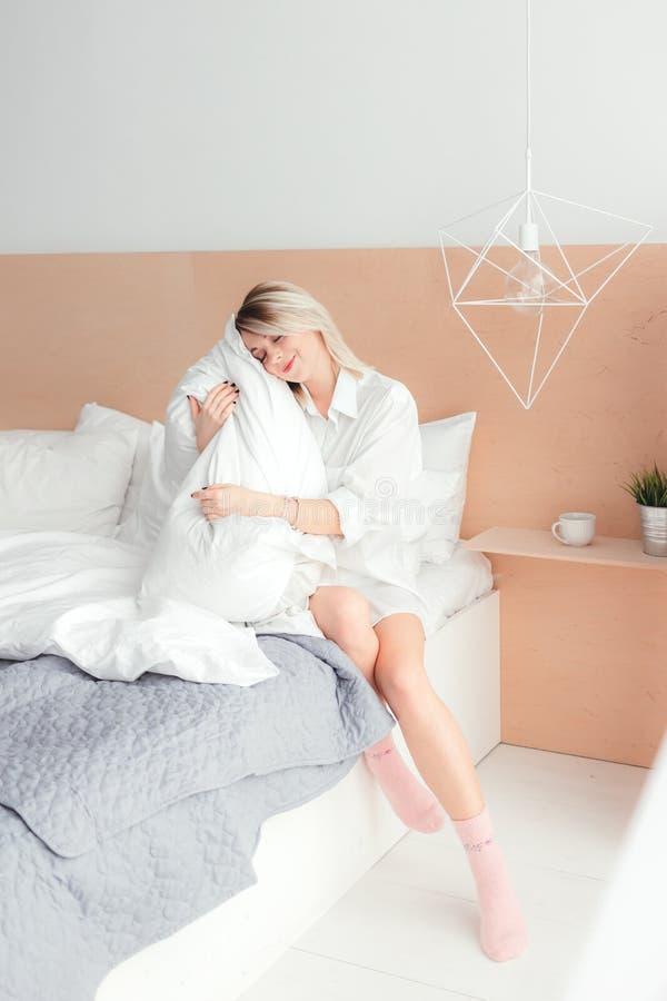 Retrato de la mujer joven hermosa que sostiene una almohada fotografía de archivo