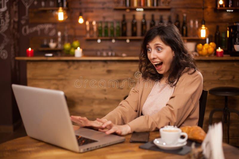 Retrato de la mujer joven hermosa sorprendida que se sienta delante de su ordenador portátil en una cafetería fotos de archivo libres de regalías