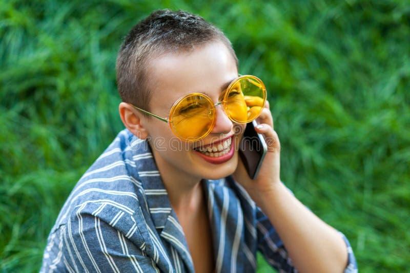Retrato de la mujer joven linda feliz con el pelo corto en el traje rayado azul casual, la camisa amarilla y los vidrios sentánd foto de archivo libre de regalías