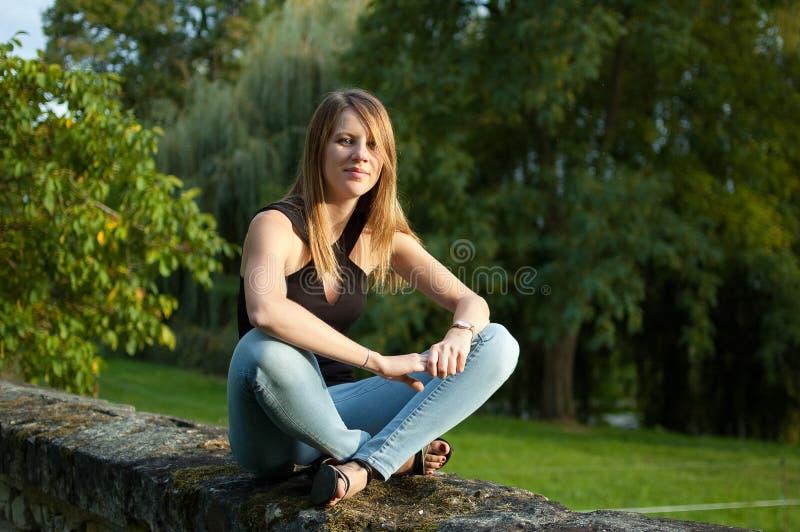 Retrato de la mujer joven linda que se sienta en el parque durante puesta del sol en vaqueros y camisa negra foto de archivo