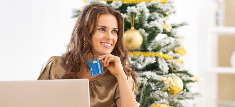 Retrato de la mujer joven pensativa con la tarjeta de crédito usando el ordenador portátil fotografía de archivo libre de regalías