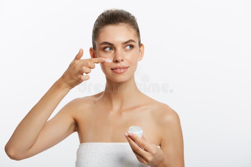 Retrato de la mujer joven que aplica la crema de la crema hidratante en su cara bonita Aislado en el fondo blanco imagen de archivo