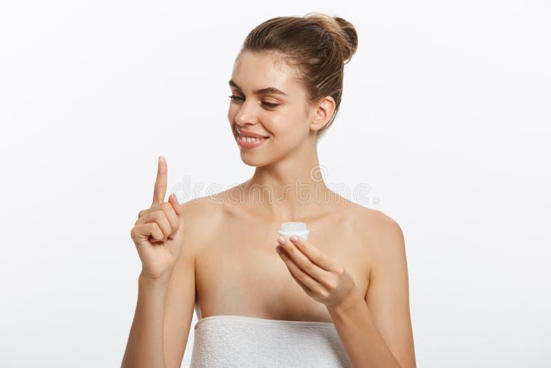 Retrato de la mujer joven que aplica la crema de la crema hidratante en su cara bonita Aislado en el fondo blanco foto de archivo libre de regalías