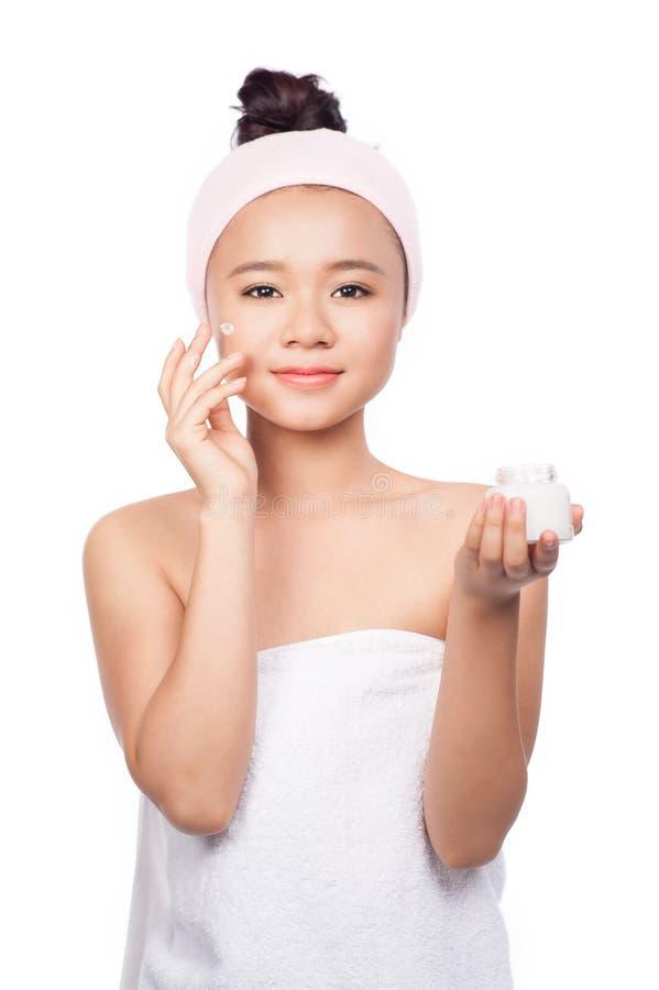 Retrato de la mujer joven que aplica la crema de la crema hidratante en su cara bonita aislada en el fondo blanco, belleza asiáti imágenes de archivo libres de regalías