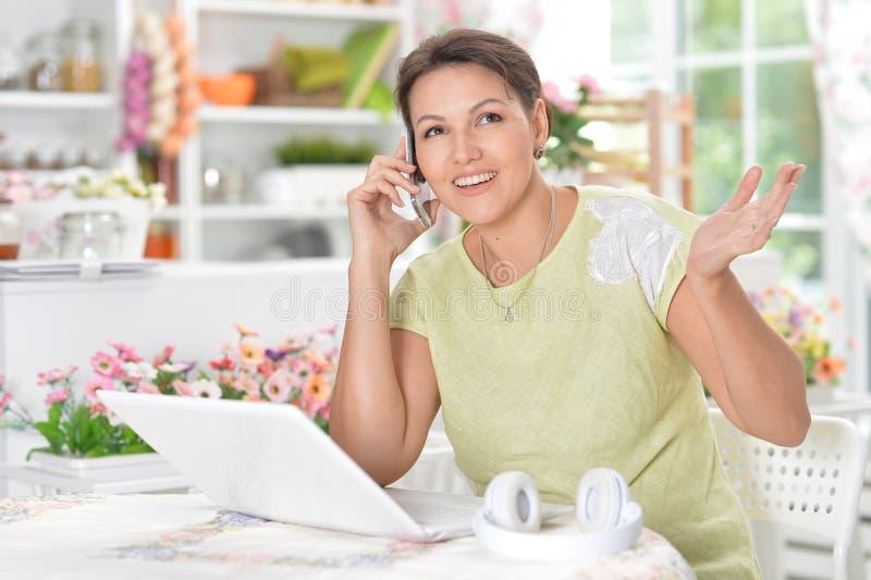 Retrato de la mujer joven que habla en el teléfono móvil mientras que se sienta en la tabla con el ordenador portátil fotografía de archivo