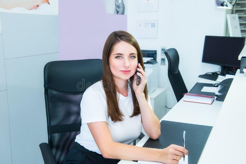 Retrato de la mujer joven que mira la cámara, hablando en el teléfono que se sienta detrás del mostrador de recepción Encargado a imagen de archivo