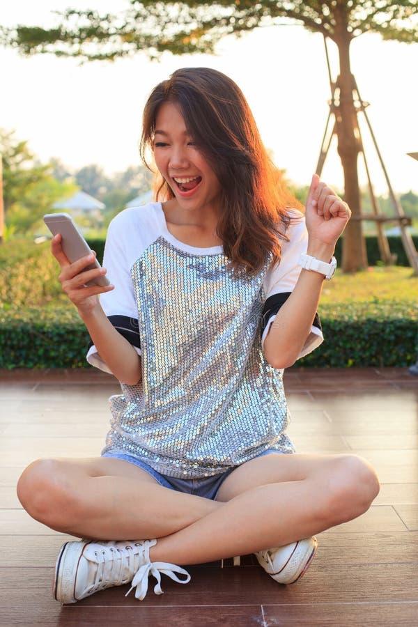 Retrato de la mujer joven que mira a la pantalla del teléfono móvil con el sur foto de archivo