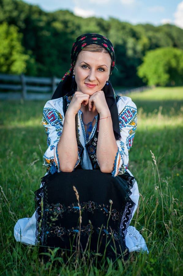 Retrato de la mujer joven que presenta en tradicional rumano imagen de archivo libre de regalías