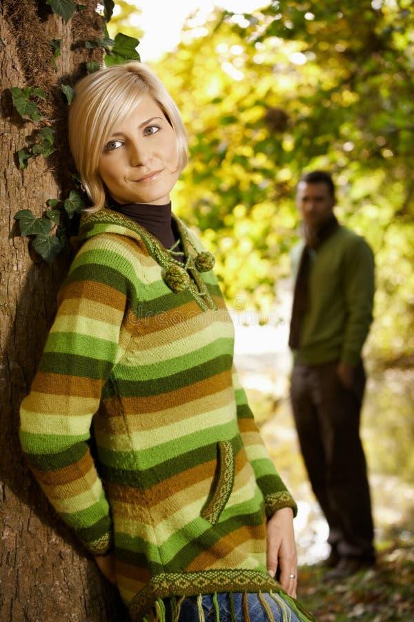 Retrato de la mujer joven que se inclina al tronco de árbol foto de archivo libre de regalías