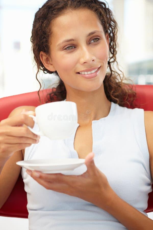 Retrato de la mujer joven que se relaja con la taza de té fotografía de archivo