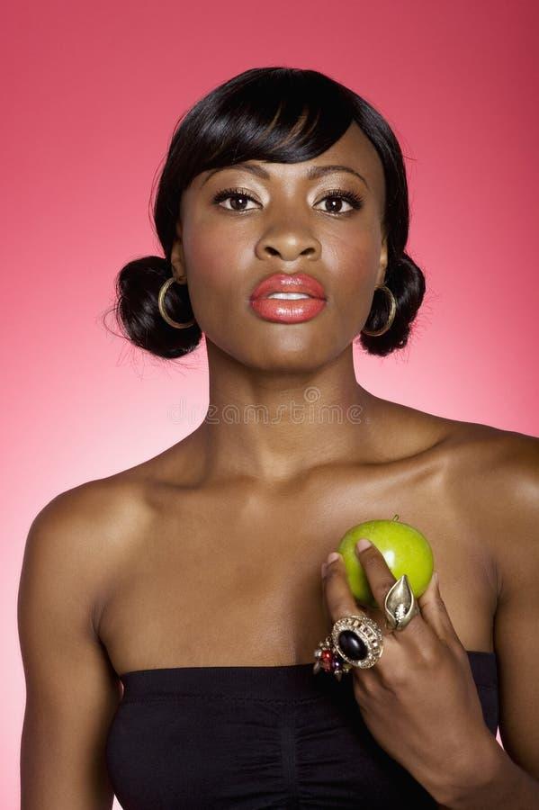 Retrato de la mujer joven que sostiene la manzana verde sobre fondo coloreado imagenes de archivo