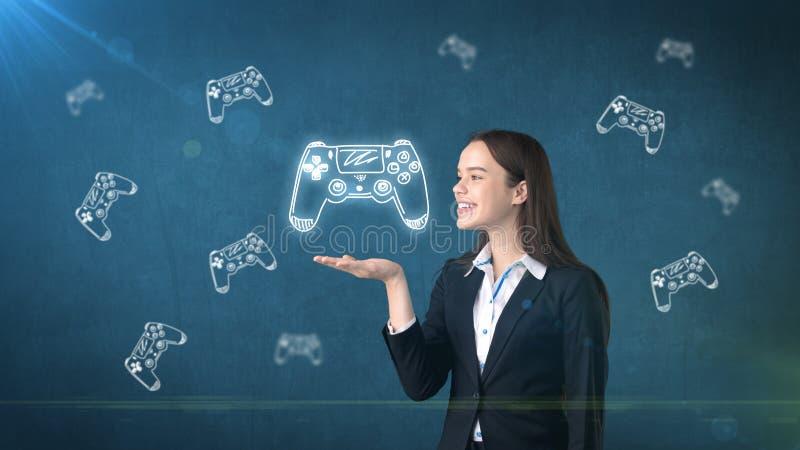 Retrato de la mujer joven que sostiene la palanca de mando del ` s del videojugador en la palma abierta de la mano, sobre fondo e imagen de archivo