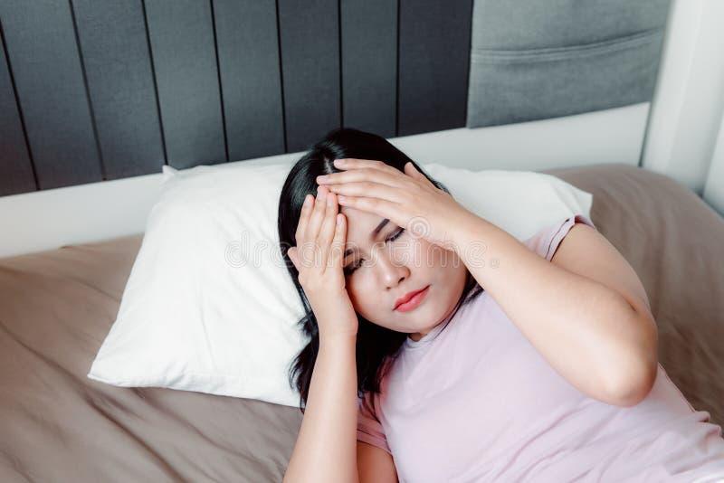 Retrato de la mujer joven que tiene depresión que sufre con dolor de cabeza de insomnio en su dormitorio , Concepto de la atenci? fotos de archivo libres de regalías
