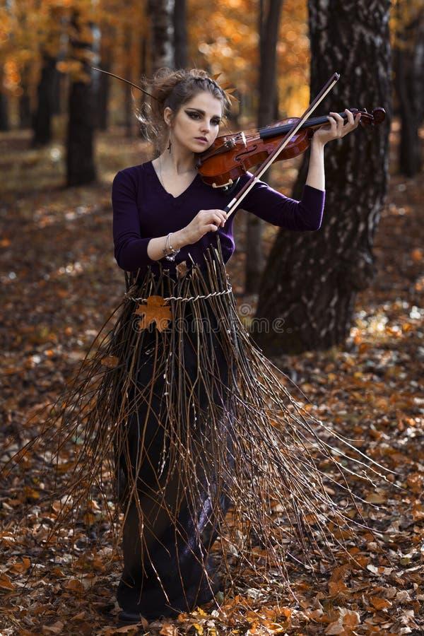 Retrato de la mujer joven que toca el violín en el parque de la caída imagen de archivo libre de regalías