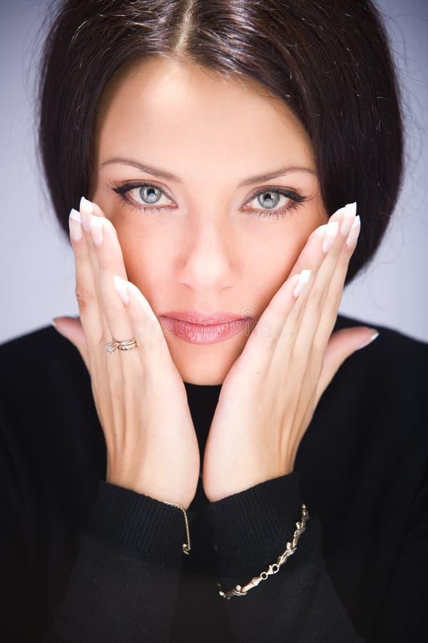 Retrato de la mujer joven que toca su cara imagenes de archivo