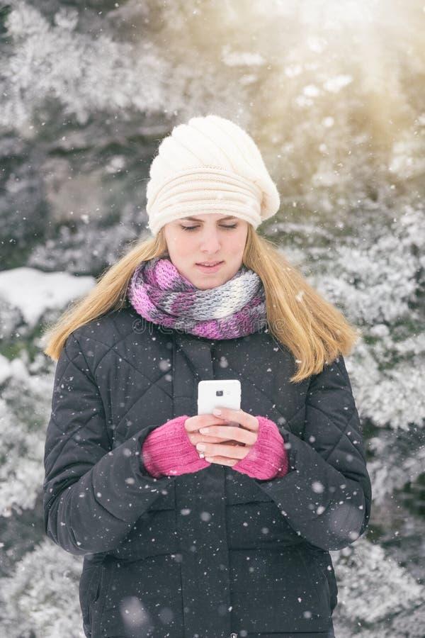 Retrato de la mujer joven que usa smartphone en día nevoso fotografía de archivo libre de regalías