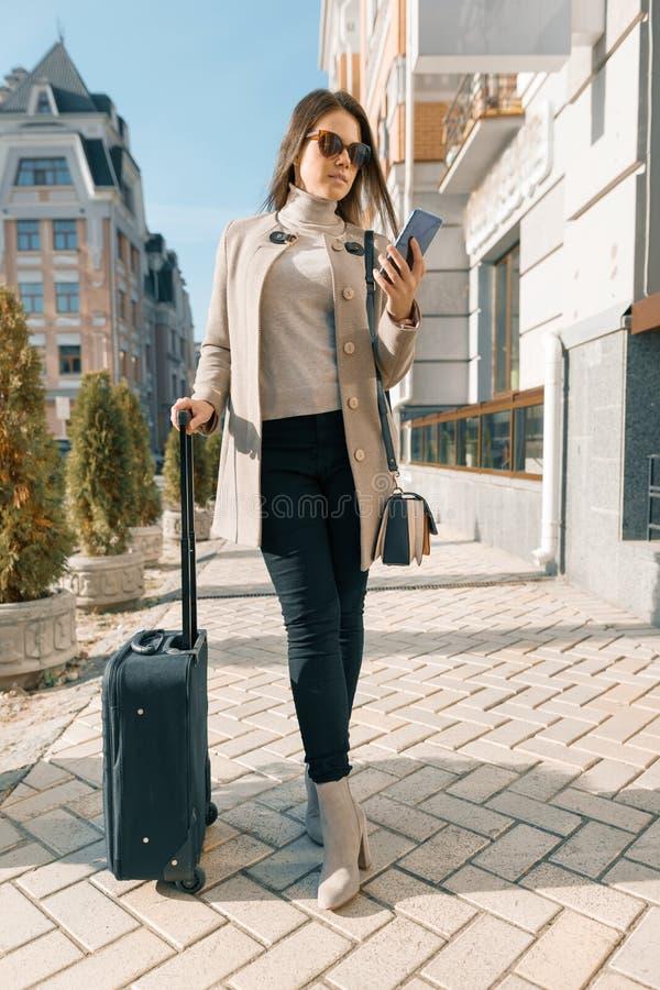 Retrato de la mujer joven que viaja con el teléfono móvil y la maleta, muchacha de moda en la calle de la ciudad, capa caliente q fotografía de archivo libre de regalías