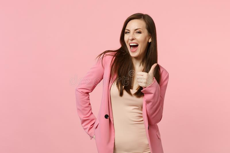 Retrato de la mujer joven de risa alegre en la chaqueta que mira la cámara, mostrando el pulgar encima de aislado en la pared ros foto de archivo libre de regalías