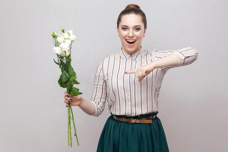 Retrato de la mujer joven romántica atractiva sorprendida en camisa rayada y ramo verde de la tenencia de la falda de flores blan imagenes de archivo