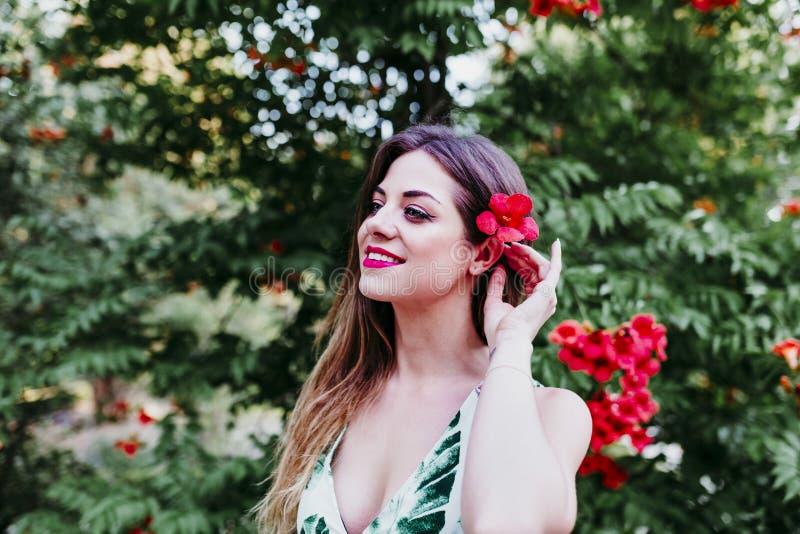 Retrato de la mujer joven rubia hermosa que sonríe en la puesta del sol El jugar con las flores rojas Concepto de la felicidad y  fotografía de archivo libre de regalías
