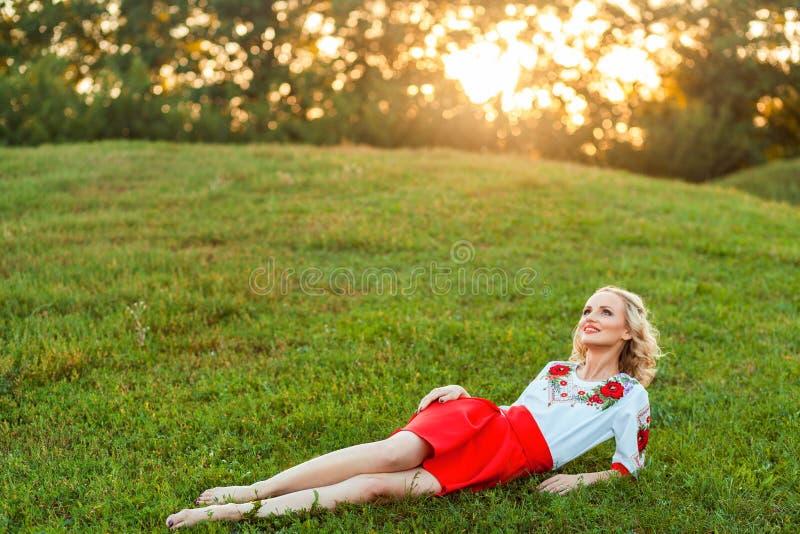Retrato de la mujer joven rubia hermosa soñadora con el peinado rizado en el vestido elegante que presenta con felicidad en hierb imágenes de archivo libres de regalías
