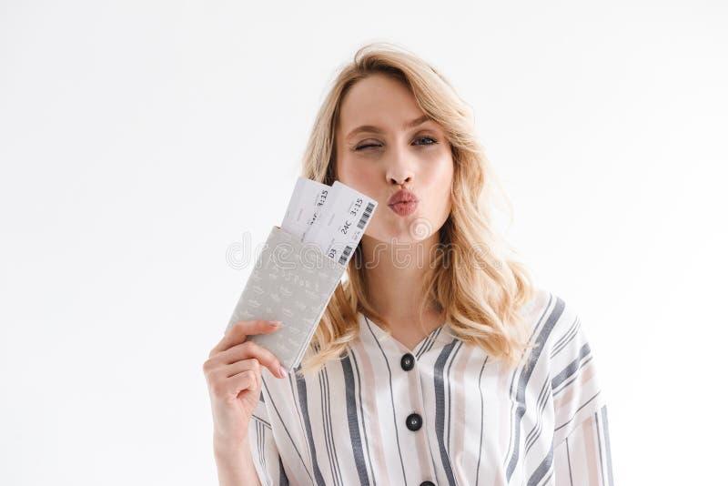 Retrato de la mujer joven rubia que lleva la ropa casual que gui?a mientras que sostiene boletos y el pasaporte que viajan imagenes de archivo