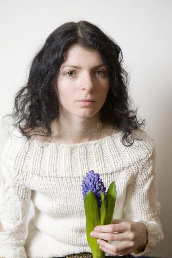 Retrato de la mujer joven seria con el jacinto foto de archivo