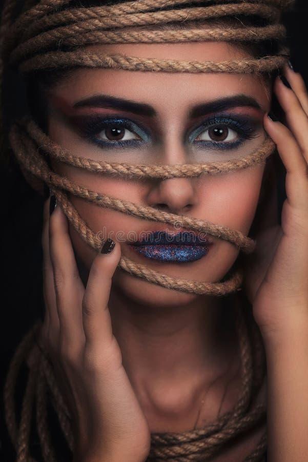 Retrato de la mujer joven sobre cuerda con el fondo negro Moda, maquillaje extraordinario y concepto de la elevación de cara imagen de archivo