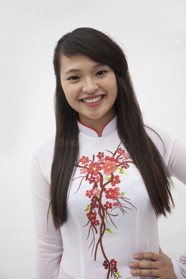 Retrato de la mujer joven sonriente con el pelo largo que lleva un vestido tradicional de Vietnam, tiro del estudio fotos de archivo libres de regalías