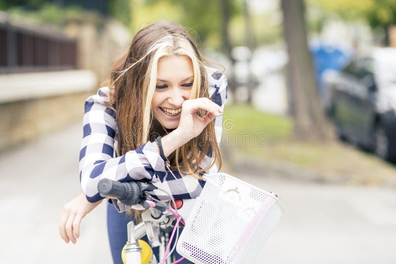 Retrato de la mujer joven sonriente con la bicicleta en la calle fotos de archivo libres de regalías