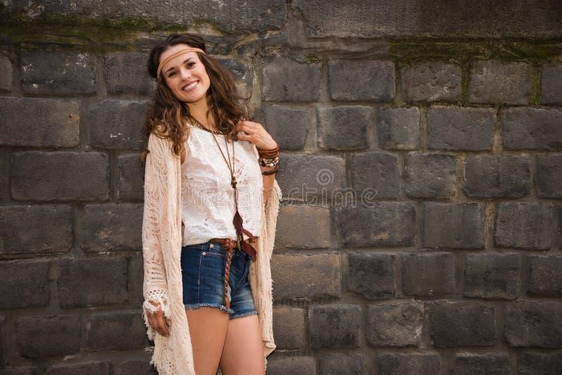 Retrato de la mujer joven sonriente del boho cerca de la pared de piedra imagen de archivo
