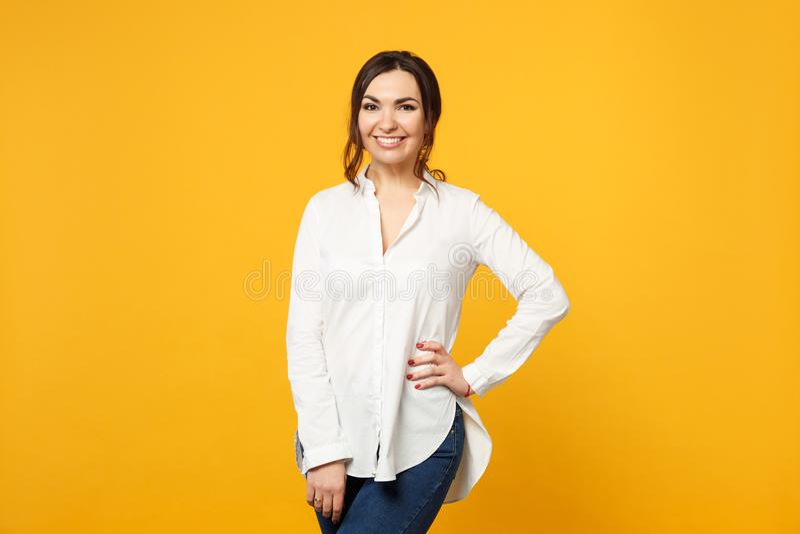 Retrato de la mujer joven sonriente en la camisa blanca, vaqueros que colocan y que miran la cámara aislada en la pared amarillo- imagenes de archivo