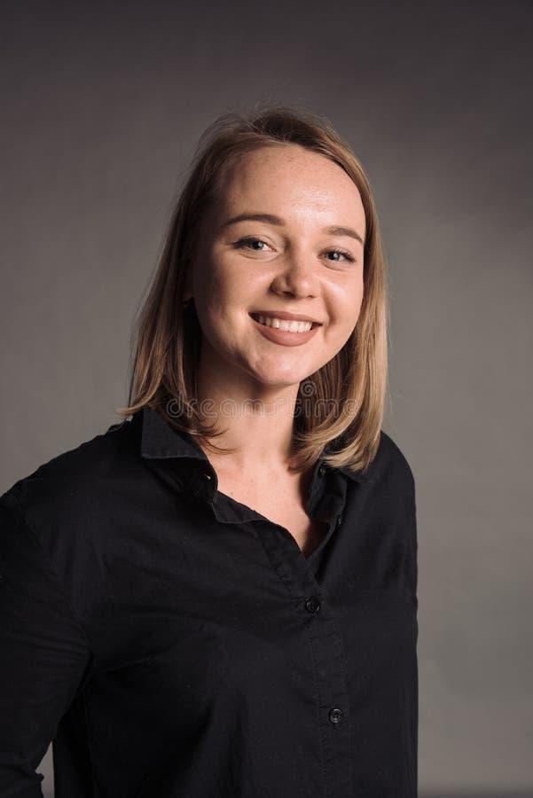 Retrato de la mujer joven sonriente en camisa negra en el fondo gris del estudio que presenta a la cámara imágenes de archivo libres de regalías