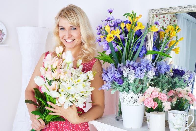 Retrato de la mujer joven sonriente en flowershop imagenes de archivo