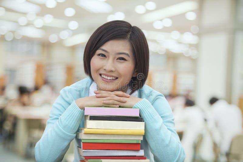 Retrato de la mujer joven sonriente en la biblioteca que se inclina en una pila de libros, mirando la cámara fotografía de archivo