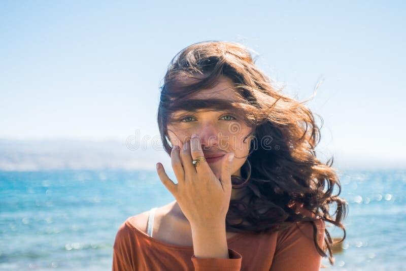 Retrato de la mujer joven sonriente feliz en fondo de la playa y del mar Juegos del viento con el pelo largo de la muchacha imagen de archivo
