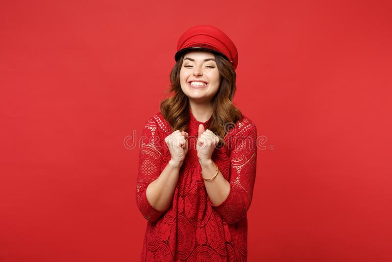 Retrato de la mujer joven sonriente feliz extática en los puños de apretón del vestido y del casquillo del cordón aislados en la  imagenes de archivo