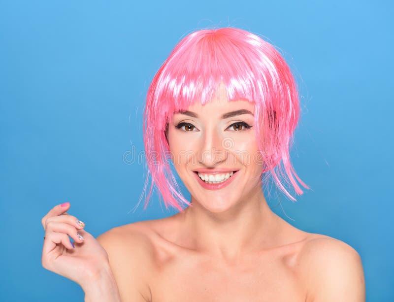 Retrato de la mujer joven sonriente hermosa con el pelo rosado en un fondo azul foto de archivo