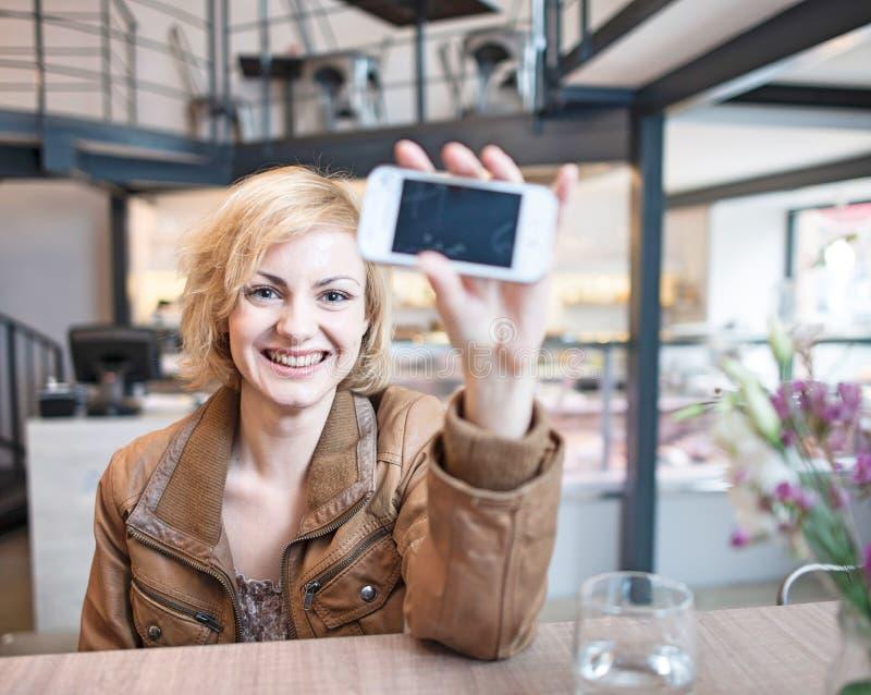 Retrato de la mujer joven sonriente que exhibe el teléfono celular en café fotografía de archivo