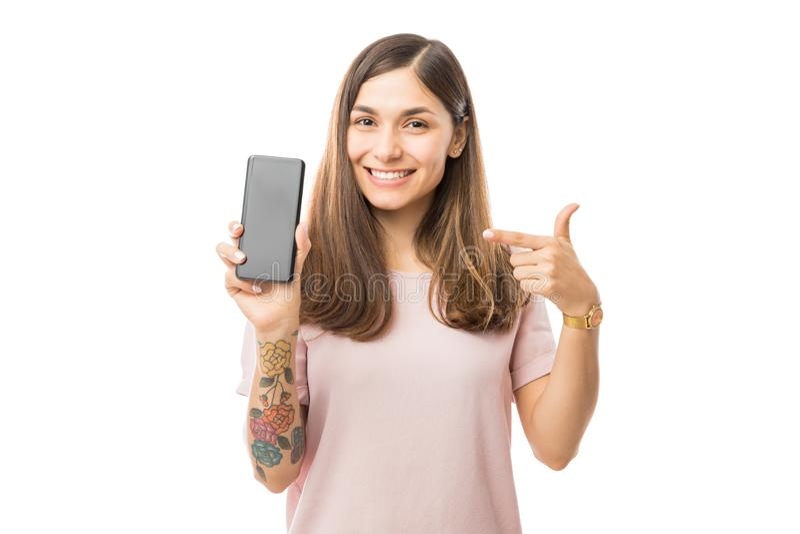 Retrato de la mujer joven sonriente que señala en nuevo Smartphone fotos de archivo