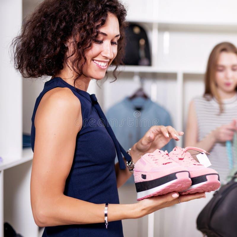 Retrato de la mujer joven sonriente que sostiene un par de nuevas zapatillas de deporte rosadas que miran felices con su compra e fotos de archivo libres de regalías